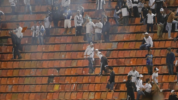 Brazil's Santos soccer fans throw seats and light flares from the grand stand after their team lost, on aggregate, a Copa Libertadores soccer match to Argentina's Independiente, in Sao Paulo, Brazil, Tuesday, Aug. 28, 2018. Independent won 3-0 on aggregate. (AP Photo/Andre Penner)