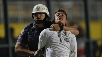 A police officer arrests a supporter of Brazil's Santos who was involved in a fight at the end of a Copa Libertadores soccer match between his team and Argentina's Independiente, in Sao Paulo, Brazil, Tuesday, Aug. 28, 2018. Independent won 3-0 on aggregate. (AP Photo/Andre Penner)