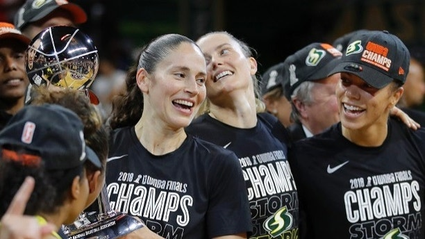 Seattle Storm guard Sue Bird, left, holds the championship trophy with her teammates during after winning Game 3 of the WNBA basketball finals, Wednesday, Sept. 18 2018, in Fairfax, Va. Seattle Storm won 98-82. (AP Photo/Carolyn Kaster)