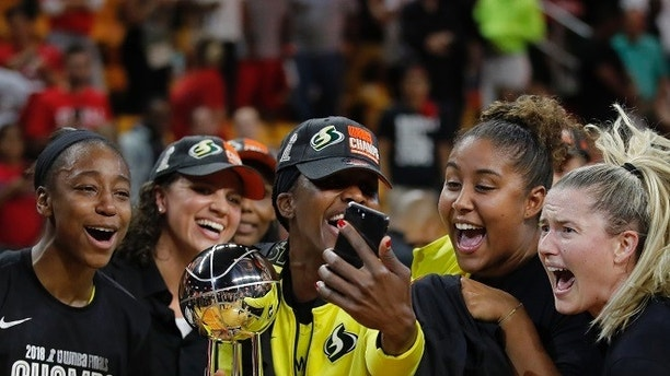 Members of the Seattle Storm celebrate and take photos with the championship trophy on the court after winning Game 3 of the WNBA basketball finals, Wednesday, Sept. 18 2018, in Fairfax, Va. The Seattle Storm defeated the Washington Mystics 98-82. (AP Photo/Carolyn Kaster)