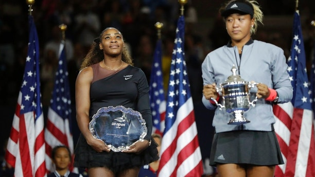 Serena Williams watches as Naomi Osaka, of Japan, binds a champions prize in a women's final of a U.S. Open tennis tournament, Saturday, Sept. 8, 2018, in New York. (AP Photo/Julio Cortez)