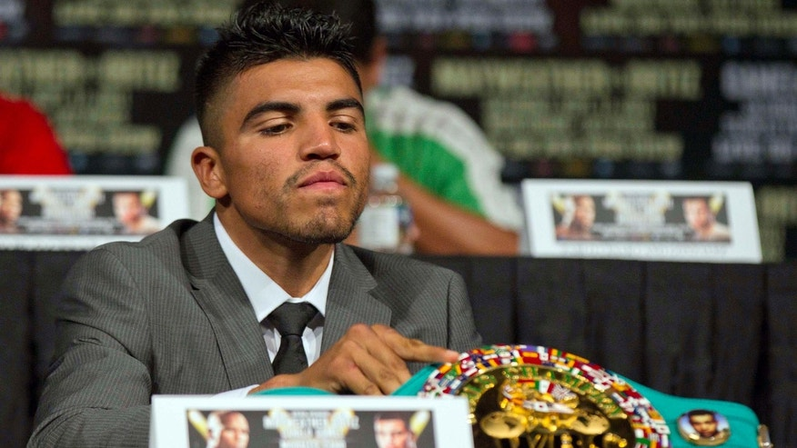 Victor Ortiz displays his WBC welterweight title belt on the table during a boxing news conference, Wednesday, Sept. 14, 2011, in Las Vegas. Ortiz is slated to defend hist title against Floyd Mayweather on Saturday, Sept. 17. (AP Photo/Julie Jacobson)