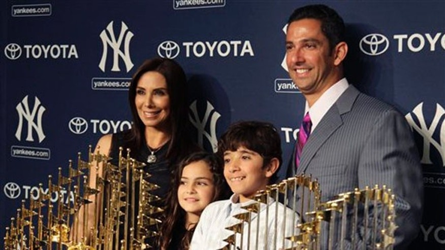 New York Yankees' Jorge Posada, right, poses for a picture with five World Series trophies and his family, wife Laura Posada, left, and children Paulina Posada, second from left, and Jorge Posda Jr. during a baseball news conference at Yankee Stadium in New York, Tuesday, Jan. 24, 2012.  Posada announced his retirement Tuesday. (AP Photo/Seth Wenig)