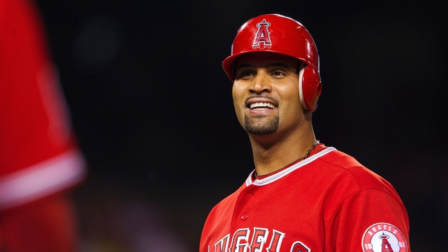 Los Angeles Angels' Albert Pujols speaks to first base coach Alfredo Griffin during a pitching change for the Los Angeles Dodgers during the third inning of a spring training baseball game, Monday, April 2, 2012, in Anaheim, Calif.