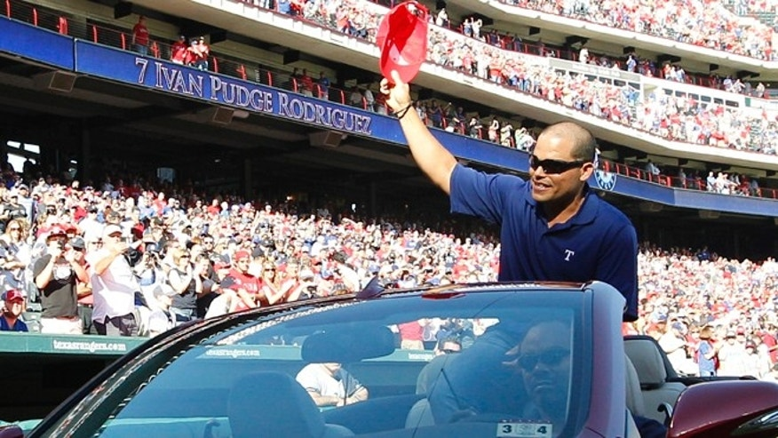 Former Texas Rangers catcher Ivan Rodriguez rides into the stadium and waves to fans before the baseball game between the New York Yankees and the Rangers on Monday, April 23, 2012, in Arlington, Texas. Rodriguez announced his retirement earlier Monday. (AP Photo/LM Otero)