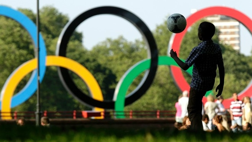 A boy plays soccer at Battersea Park while a set of Olympic rings located on a barge floats in the River Thames in the distance Sunday, July 22, 2012, in London. The city will host the 2012 London Olympics which opens Friday, July 27. (AP Photo/Charlie Riedel)