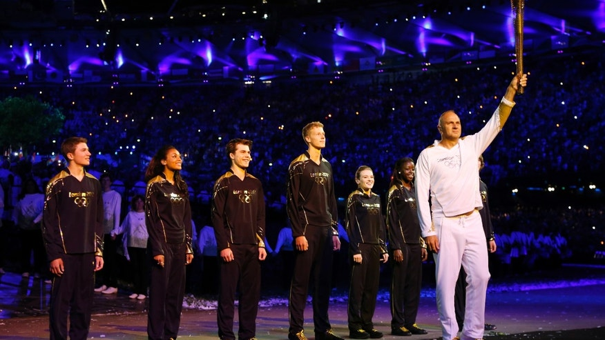 July 27, 2012: Steve Redgrave, right, holds the Olympic torch after entering the stadium during the Opening Ceremony at  the 2012 Summer Olympics.
