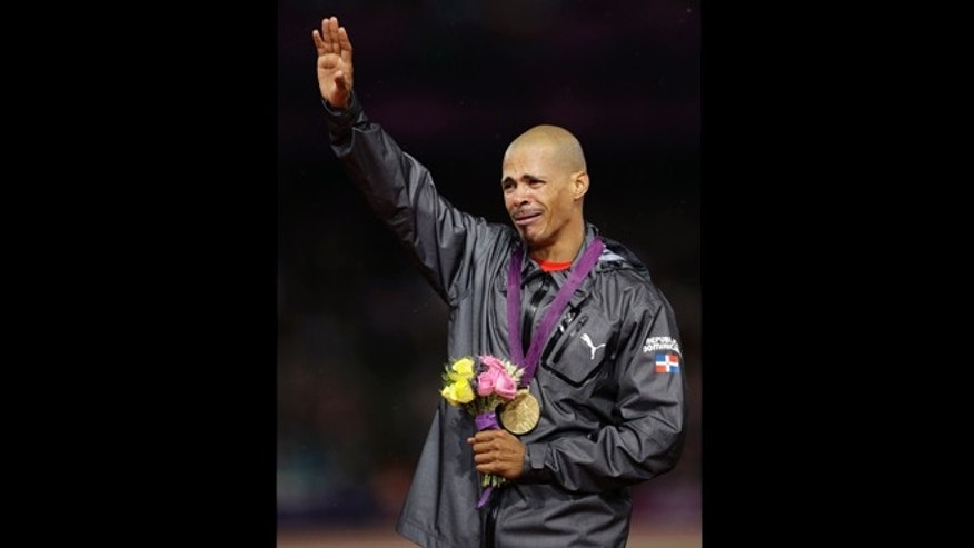 Dominican Republic's gold medalist in the men's 400-meter hurdles final, Felix Sanchez waves from the podium in the Olympic Stadium at the 2012 Summer Olympics, London, Monday, Aug. 6, 2012. (AP Photo/Matt Slocum)