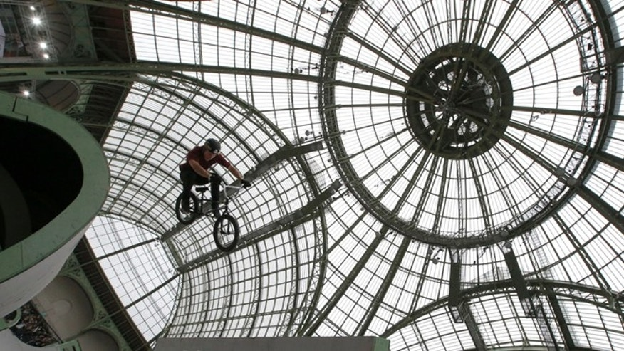 Dennis Enarson of the U.S. performs an aerial trick with his BMX bike during a training session at The Grand Palais in Paris, Friday, Nov. 2, 2012. (AP Photo/Francois Mori)