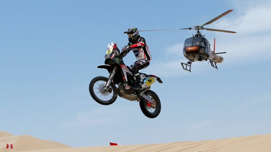 Husqvarna rider Joan Barreda Bort of Spain competes in the stage one as a helicopter flies above during the 2013 Dakar Rally between Lima and Pisco, Peru, Saturday, Jan. 5, 2013. The race finishes in Santiago, Chile, on Jan. 20. (AP Photo/Victor R. Caivano)