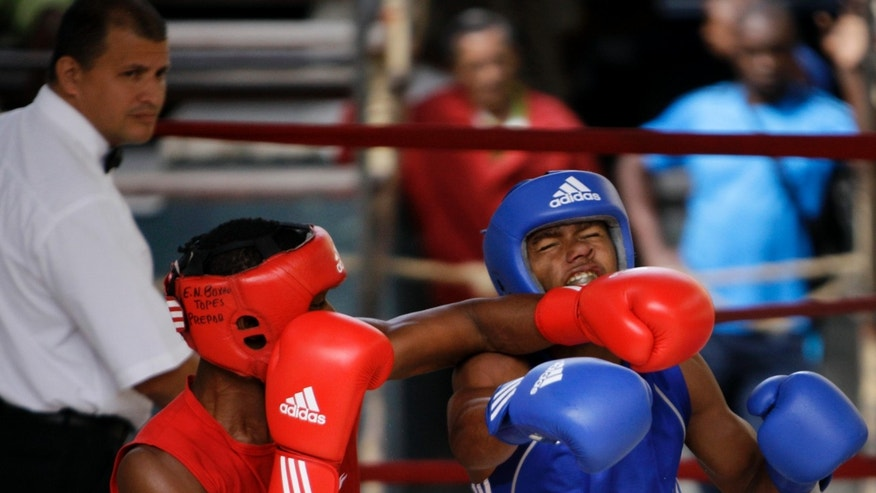 In this March 16, 2013 photo, boxer Barbaro Pedroso, left, fights with Victor Aguila in a boxing tournament at the Rafael Trejos boxing gym in Old Havana, Cuba. In 2011, the country lowered the age of competition from 11 to 9 years old, beginning with a pilot program in Havana, in line with many other countries' boxing programs, and going semi-pro could be the next step toward regaining Olympic glory. (AP Photo/Franklin Reyes)