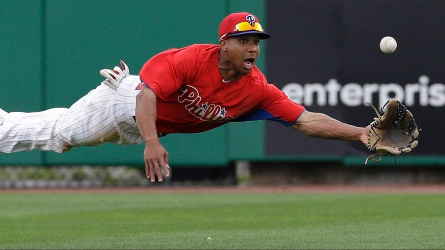 Philadelphia Phillies center fielder Ben Revere makes a diving catch of Will Middlebrooks's seventh-inning fly ball in a spring training baseball game against the Boston Red Sox in Clearwater, Fla., Sunday, March 24, 2013.  (AP Photo/Kathy Willens)