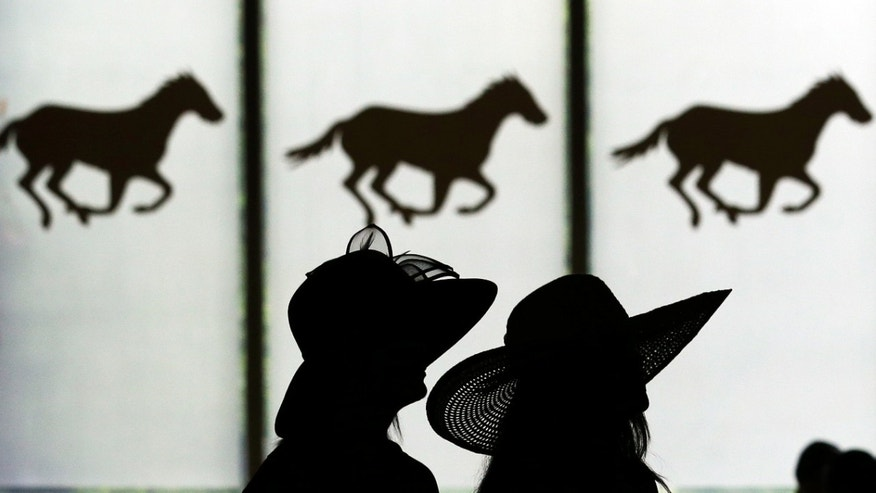 Two women are silhouetted against a window featuring race horses at Belmont Park in Elmont, N.Y., Saturday, June 9, 2012. The Belmont Stakes will be run at the track later in the day. (AP Photo/Julio Cortez)