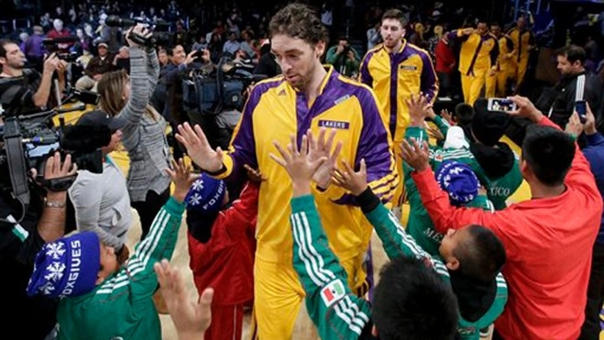 Members of The Triqui kids basketball team, made up of children from the mountainous region of the Mexican state of Oaxaca greet Los Angeles Lakers center Pau Gasol before an NBA basketball game against the Minnesota Timberwolves in Los Angeles, Friday, Dec. 20, 2013. (AP Photo/Chris Carlson)
