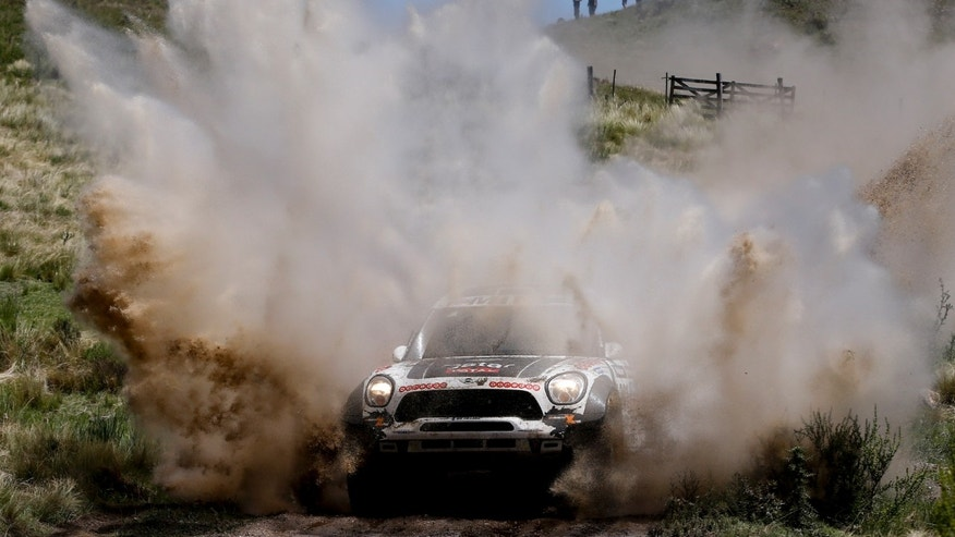Mini driver Nasser Al-Attiyah, of Qatar, and co-pilot Lucas Cruz, of Spain, race through a creek during the first stage of the Dakar Rally between the cities of Rosario and San Luis, Argentina, Sunday, Jan. 5, 2014. (AP Photo/Victor R. Caivano)