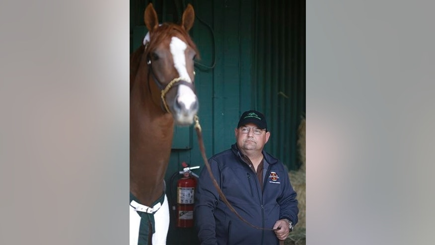 Assistant trainer Alan Sherman stands with Kentucky Derby and Preakness Stakes winner California Chrome during a walk at Pimlico Race Course in Baltimore, Monday, May 19, 2014. California Chrome is scheduled to depart Tuesday for Belmont Park, N.Y. The Belmont Stakes horse race takes place June 7. (AP Photo/Patrick Semansky)