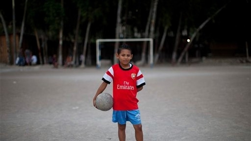 "In this Monday, March 3, 2014 photo, 11-year-old Maynor Ayala holds a soccer ball as he poses for a portrait before practice at his neighborhood's pitch in Progreso, Tegucigalpa, Honduras. Maynor allows himself to imagine going all the way to the World Cup one day, just like one of his heroes, Emilio Izaguirre, who will play in Brazil this summer on the Honduran national team. ""I want to be a soccer player,"" Maynor says. (AP Photo/Dario Lopez-Mills)"