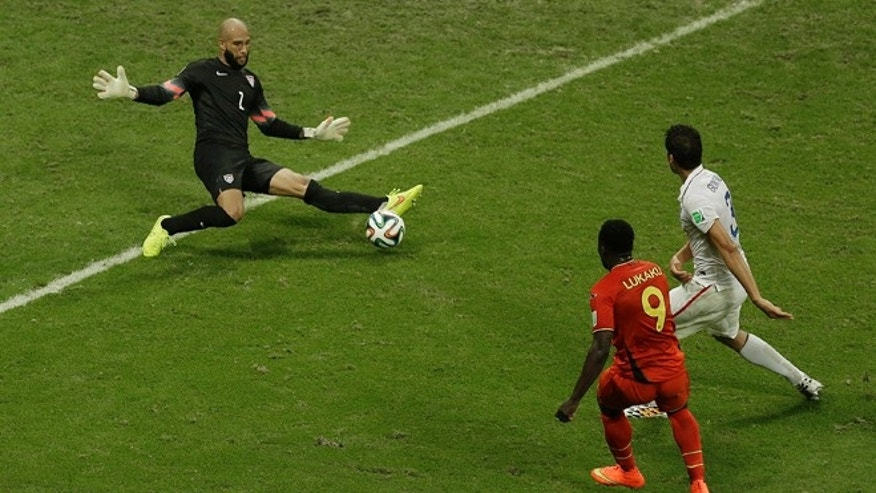 United States' goalkeeper Tim Howard, left, makes a save as Belgium's Romelu Lukaku, front, looks on during the World Cup round of 16 soccer match between Belgium and the USA at the Arena Fonte Nova in Salvador, Brazil, Tuesday, July 1, 2014. (AP Photo/Themba Hadebe)