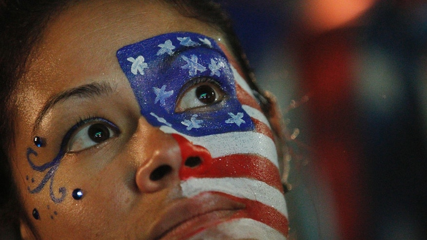 A fan of the U.S. national soccer team, with her face painted with the nation's colors watches her team's World Cup round of 16 match against Belgium on a live telecast inside the FIFA Fan Fest area on Copacabana beach in Rio de Janeiro, Brazil, Tuesday, July 1, 2014. Belgium beat the United States 2-1 in extra time to reach World Cup quarterfinals. (AP Photo/Leo Correa)
