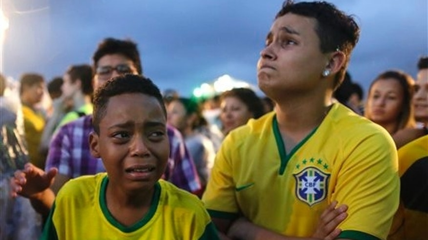 Brazil soccer fans cry as they watch their team get beat during a live telecast of the semi-finals World Cup soccer match between Brazil and Germany, inside the FIFA Fan Fest area on Copacabana beach in Rio de Janeiro, Brazil, Tuesday, July 08, 2014. (AP Photo/Leo Correa)