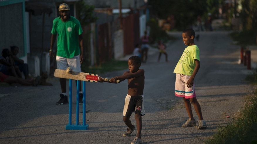 In this Sept. 29, 2014 photo, Yordeni Caballeros, center, bats the ball while his friend Duani Rojas, right, and his coach Kiomai Aguiar, left, watch during a game of street cricket in the neighborhood of San Miguel del Padrón in Havana, Cuba, Monday, Sept. 29, 2014. The Caribbean is divided between baseball-playing countries with U.S. ties and cricket-playing islands that once belonged to the British Empire. Nowhere is more baseball-crazy than Cuba, but even here, a tiny but passionate group of men is trying to win people over to cricket (AP Photo/Ramon Espinosa)
