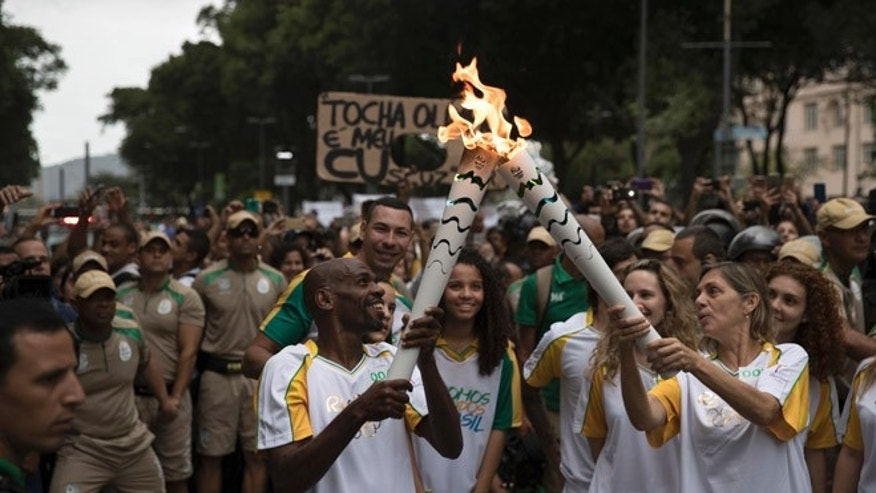 Brazilian garbage collector and dancer Renato Sorriso, left, passes the Olympic flame to Brazilian actress Carla Camurati, on its way for the opening ceremony of Rio's 2016 Summer Olympics, in Rio de Janeiro, Brazil, Wednesday, Aug. 3, 2016. The flame will make its way to Maracana Stadium for the opening ceremony on Friday. (AP Photo/Felipe Dana)
