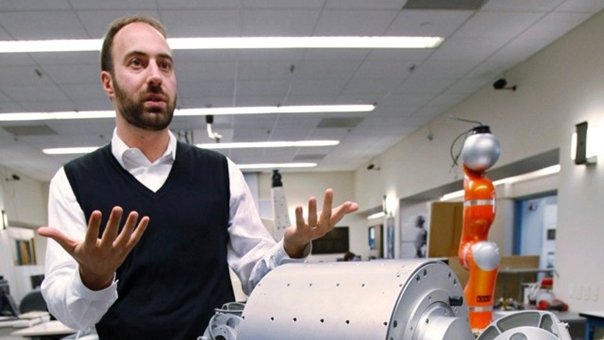 Ryan Calo, with the Stanford Center for Internet and Society at the Stanford Law School, stands next to a robot that is being built for medical applications at Stanford University's Artificial Intelligence Laboratory in Palo Alto, Calif.