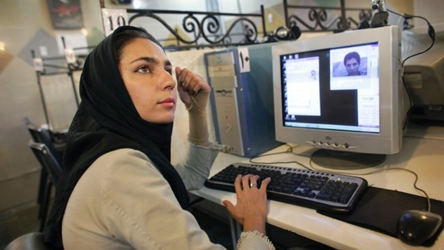 An Iranian woman who declined to give her name uses the Internet at an net cafe in northern Tehran, Iran. Iranian authorities have slowed Internet connections to a crawl or choked them off completely before expected student protests Monday, to deny the opposition a vital means of communication.