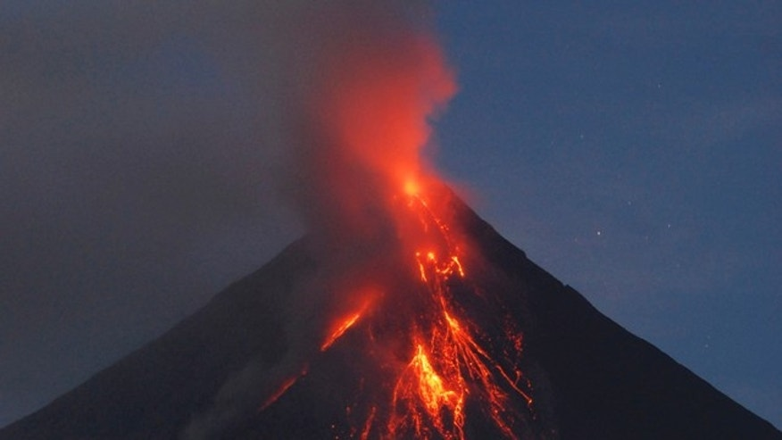 Dec. 17: Lava cascades down the slopes of the Mayon volcano in Legazpi city, Albay province, at dawn about 500 kilometers (310 miles) south of Manila, Philippines. Security forces will forcibly evacuate thousands of residents reluctant to leave their farms near the smoldering volcano, officials said.