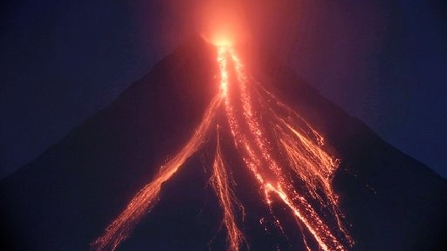 Lava cascades down the slopes of Mayon volcano in a continuing mild eruption as viewed from Legazpi city, Albay province, about 500 kilometers southeast of Manila, Philippines at dusk on Christmas eve Thursday Dec.24, 2009. Volcanologists warned that the weeklong moderate eruption of the 8,070-foot (2,460-meter) Mayon could escalate within days as the volcano belched out 20 grayish ash columns Thursday, some a mile (1.5 kilometers) high.
