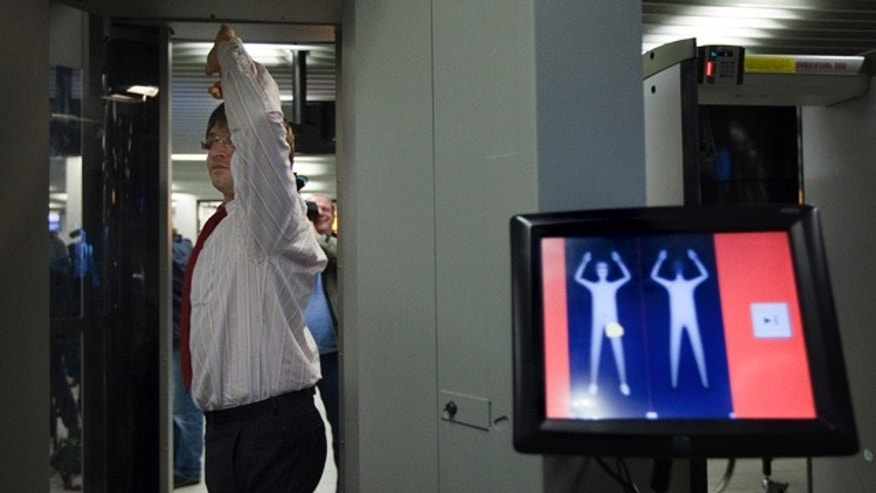 "An employee of Schiphol stands inside a body scanner during a demonstration at a press briefing at Schiphol airport, Netherlands. The Netherlands announced Wednesday, Dec. 30, it will immediately begin using full body scanners for flights heading to the United States, issuing a report that called the failed Christmas Day airline bombing a ""professional"" terror attack."