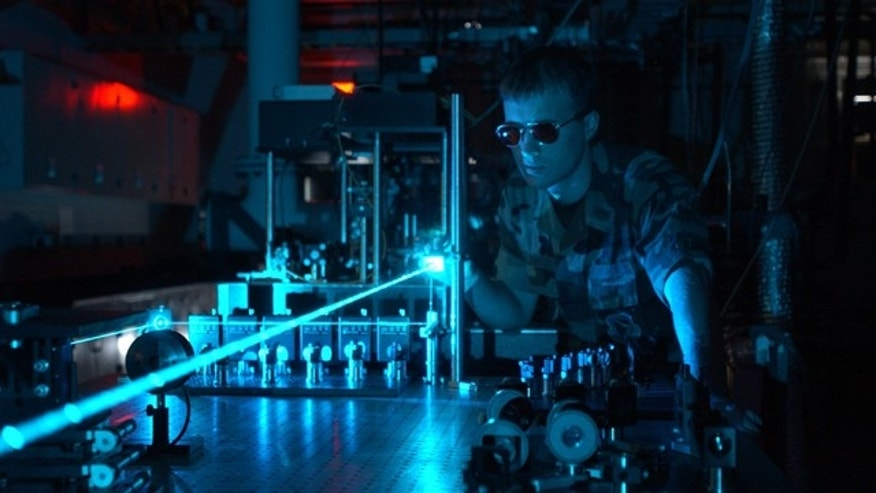A military scientist operates a laser in a test environment. The Directorate conducts research on a variety of solid-state and chemical lasers.