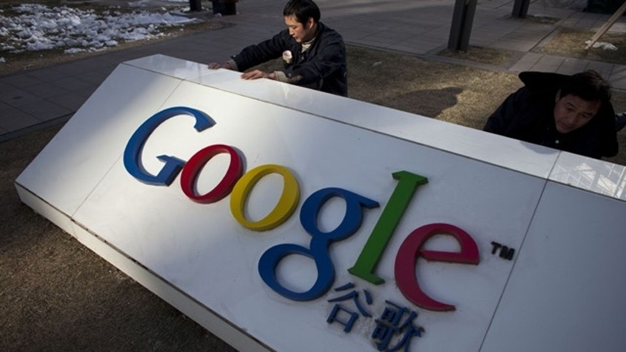 Workers repair a partially broken marble tablet which bears Google's logo in front of Google China's headquarters building in Beijing, China.