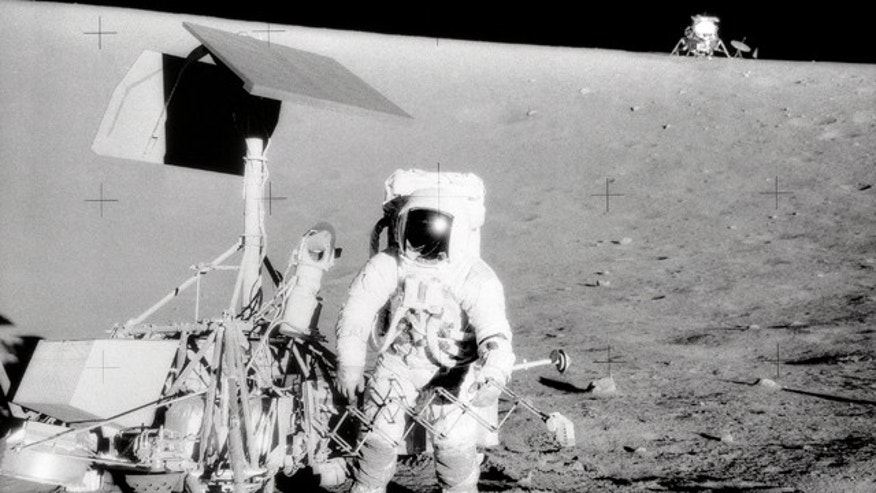 "Apollo 12 Commander Charles Conrad Jr. examines the unmanned Surveyor III spacecraft during the second extravehicular activity in 1967. The Lunar Module ""Intrepid"" is in the background."