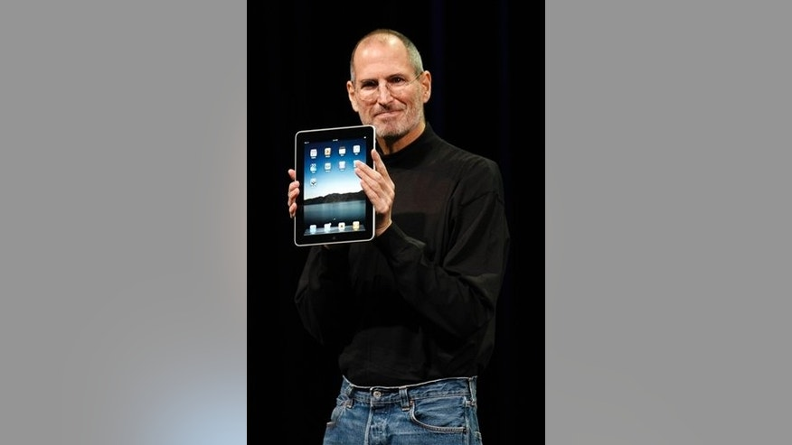 Apple CEO Steve Jobs shows off the new iPad during an Apple event in San Francisco, Wednesday, Jan. 27, 2010. (AP Photo/Paul Sakuma)
