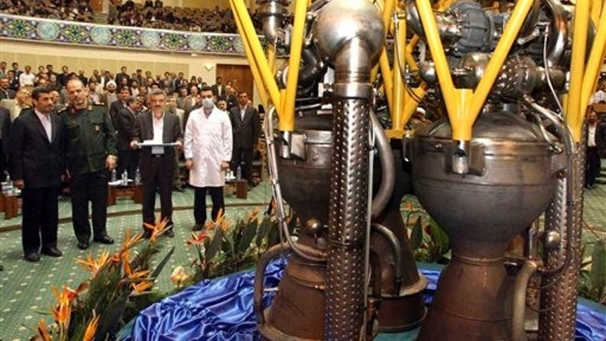 Feb. 3: Iranian President Mahmoud Ahmadinejad, left, listens to his Defense Minister Gen. Ahmad Vahidi, as he looks at engine of a domestically-built satellite booster rocket, in Tehran, Iran. President Ahmadinejad unveiled the domestically-built satellite booster rocket, part of an ambitious space program that has worried Western powers because they fear the same technology used to launch satellites could also deliver warheads.