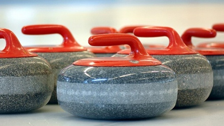 A set of curling stones rests on the ice. Each stone weighs about 41 pounds.