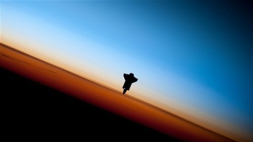 The silhouette of the space shuttle Endeavour in a very unique setting over Earth's colorful horizon  photographed by an Expedition 22 crew member prior to STS-130 rendezvous and docking operations with the International Space Station.