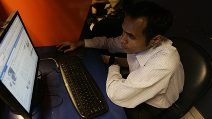 An Indonesian man checks his Facebook page at an Internet cafe in Jakarta, Indonesia, Wednesday, Feb. 17, 2010. A teenager received a suspended jail sentence for posting insulting comments on a romantic rival's Facebook page, the latest case bringing Indonesia's tough defamation laws under criticism. (AP Photo/Irwin Fedriansyah)