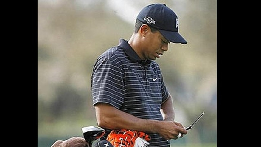 Tiger Woods checks his cell phone as he waits for his group to tee-off on the sixth hole during at the Arnold Palmer Invitational golf tournament in Orlando March 12, 2008.