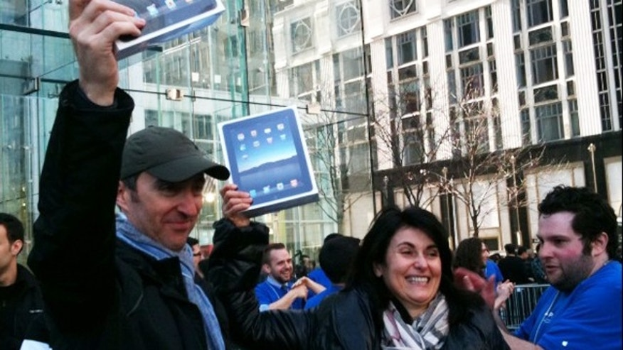 April 3: A couple holds their iPads after waiting hours on line in NYC's Apple store.  (Fox News)