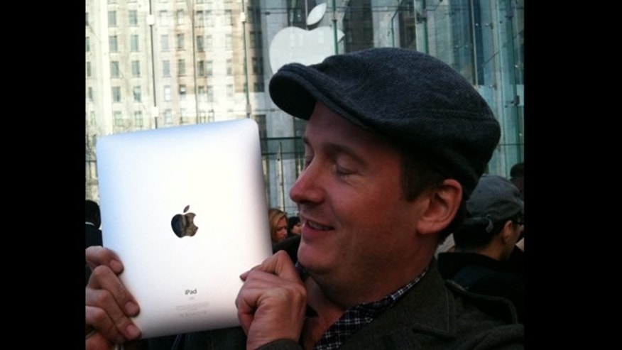 April 3: A man holds his iPad after waiting hours on line in NYC's Apple store.  (Fox News)