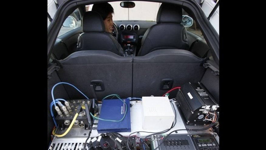 Stanford graduate student Mick Kritayakirana shows the computer system inside a driverless car on the Stanford University campus in Palo Alto, Calif.