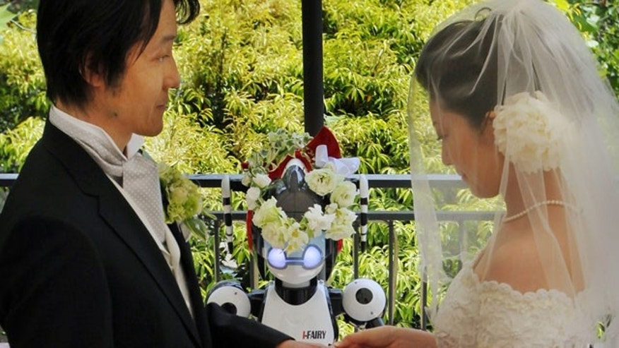 May 16: Bride Satoko Inouye, 36, puts a ring on a finger of her groom Tomohiro Shibata 42, as I-Fairy, a four-foot tall seated robot, wearing a wreath of flowers, directs their wedding ceremony at a Tokyo restaurant.
