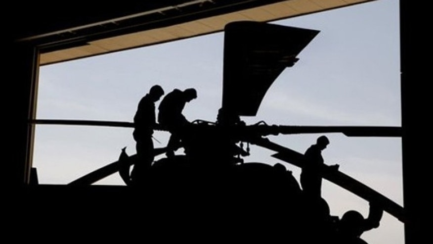 Afghan air force engineers are silhouetted as they work on an MIL-35 Russian-built helicopter inside a hanger at an air force base in Kabul, Afghanistan on April 6, 2010.