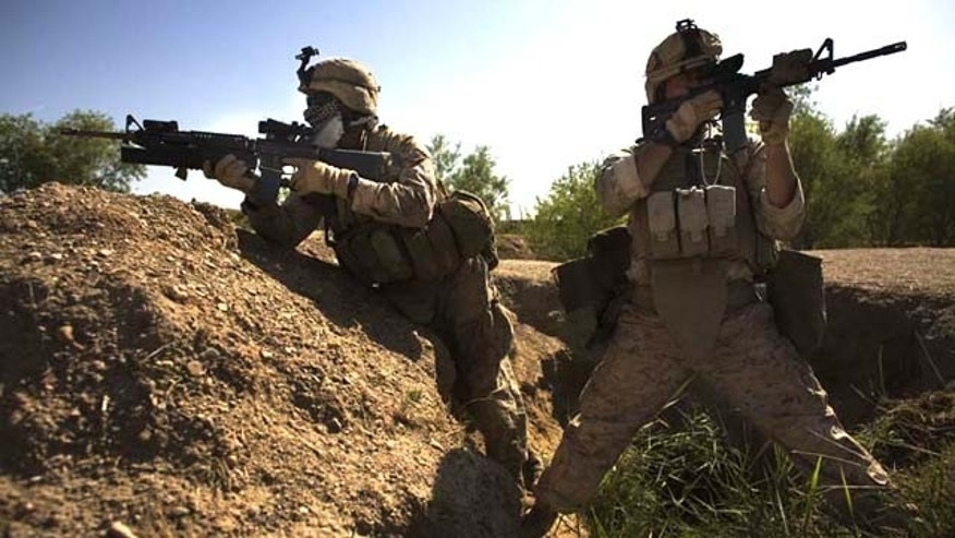 Navy corpsman Michael Lang, of Camden County, Ga., right, with an M-4 carbine, and Lance Cpl. Ard Bizahaloni of Pinon, Ariz., with an M-16 rifle, with the First Battalion, Sixth Marine Regiment, Alpha company, take up positions in Marjah, Afghanistan. The U.S. military's workhorse rifle, used in battle for the last 40 years, may be proving less effective in Afghanistan.