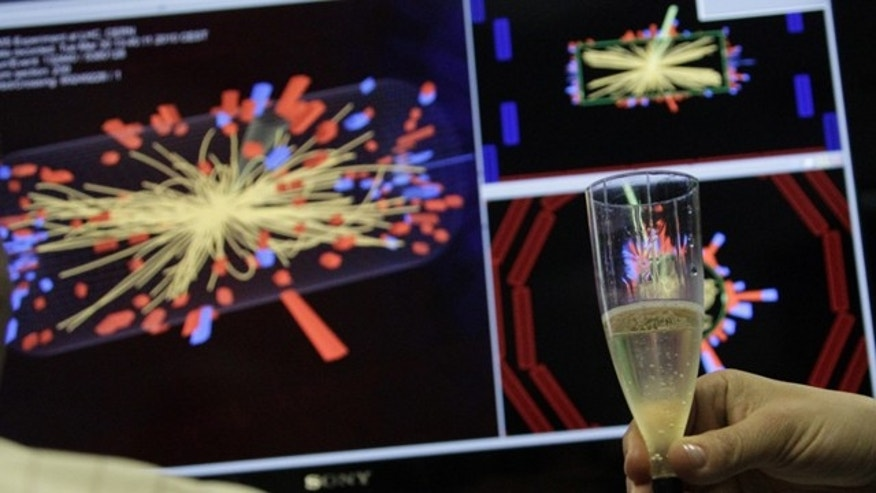 A scientist holds a glass of champagne after the first successful collisions at full power at the Compact Muon Solenoid (CMS) experience control room at the Large European Organisation for Nuclear Research (CERN) in Meyrin, near Geneva March 30, 2010.