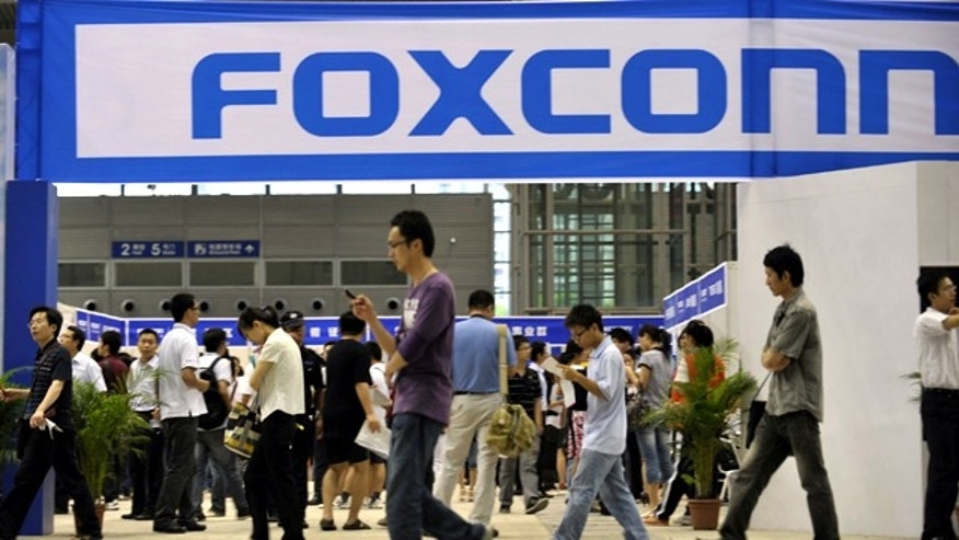 May 22, 2010: Visitors to a job fair walk past the Foxconn recruitment area in Shenzhen in south China's Guangdong province.