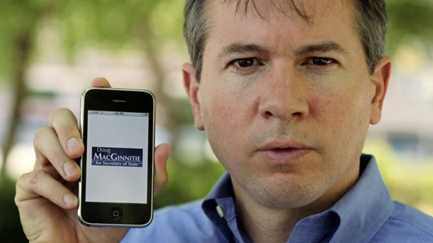 Candidate for Georgia Secretary of State Doug MacGinnitie poses with his iPhone in Atlanta. MacGinnitie had a friend created an iPhone applications so supporters can follow his campaign and make contributions.