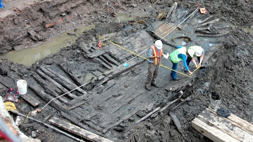 Workers at the World Trade Center in downtown Manhattan analyze a 32-foot-long ship hull found early Tuesday.